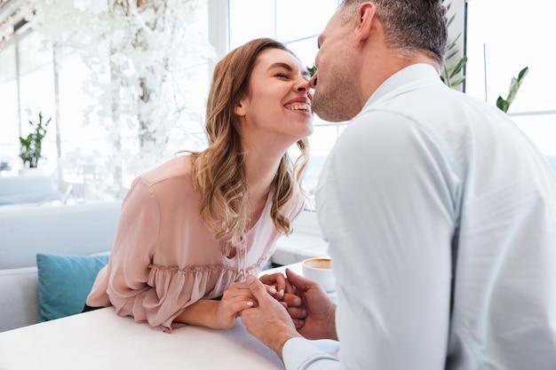Foto de casal atraente homem e mulher sendo feliz, enquanto ter data no restaurante com exibição pública de carinho