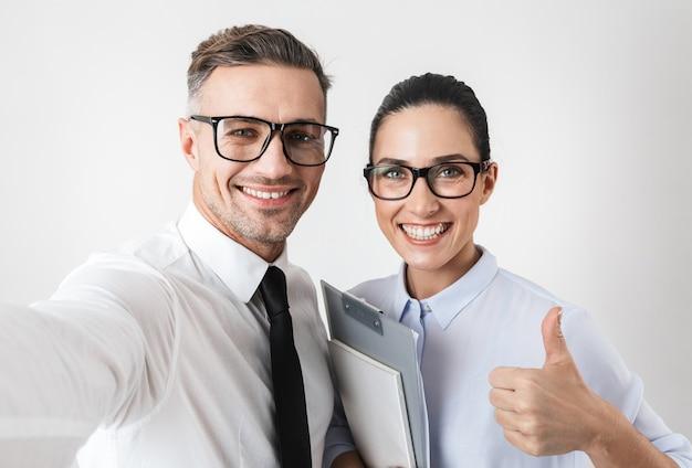 Foto de casal de colegas de trabalho feliz isolado sobre a parede branca, mostrando os polegares para cima gesto leve selfie.