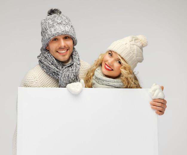 Foto de casal de família com roupas de inverno segurando um quadro em branco