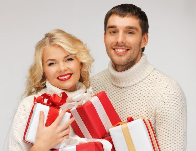 Foto de casal de família em um suéter com caixas de presente