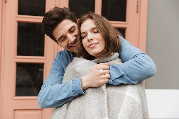 Foto de casal feliz apaixonado em pé do lado de fora do café, enquanto um homem se abraça e envolve sua mulher em um cobertor quente