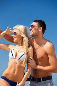 Foto de casal feliz em óculos de sol na praia.
