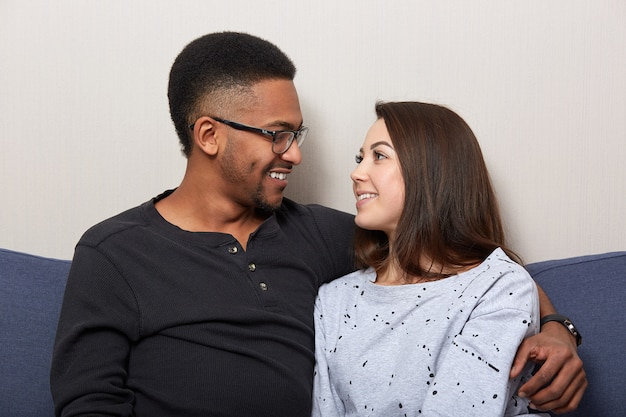 Foto de casal feliz no amor olhar sorrindo para o outro, estar em casa, passar algum tempo juntos, assistir filmes enquanto está sentado no sofá, homem e mulher no apartamento. pessoas, conceito de relacionamento interracial.