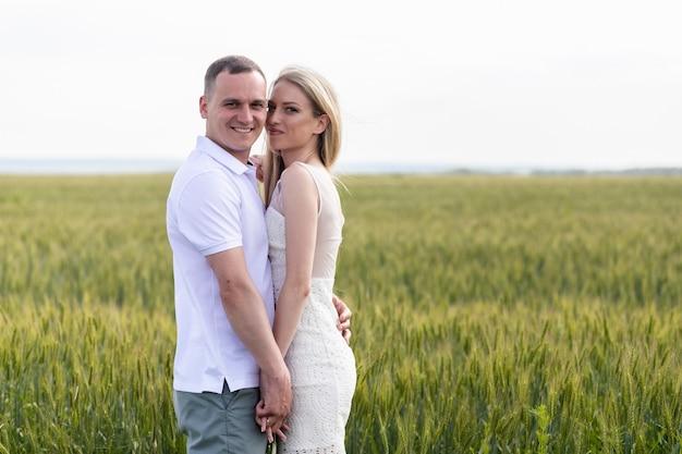 Foto de casal feliz se abraçando no campo de trigo