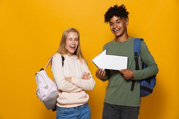 Foto de ; casal homem e mulher de 16 a 18 anos segurando o ponteiro de seta do copyspace, isolado sobre fundo amarelo