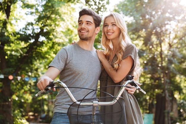 Foto de casal jovem adorável e feliz em pé com uma bicicleta