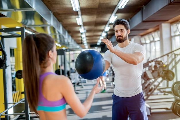 Foto de casal jovem bonito desportivo malhando juntos no ginásio. usando bolas pesadas para seu treinamento.