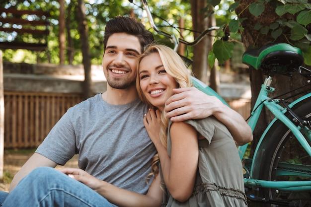 Foto de casal jovem e adorável feliz descansando juntos e olhando para a câmera ao ar livre