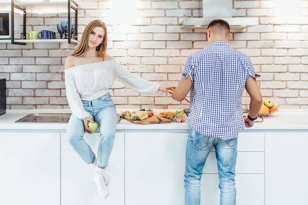 Foto de casal jovem feliz se preparando para comer na cozinha juntos.