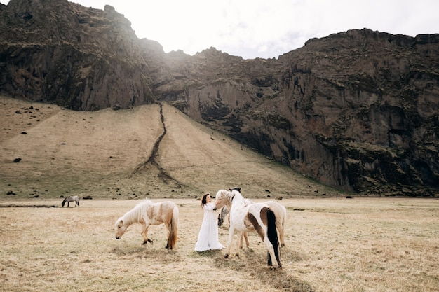Foto de casamento de uma noiva acariciando cavalos em um campo em uma montanha rochosa em um destino na islândia