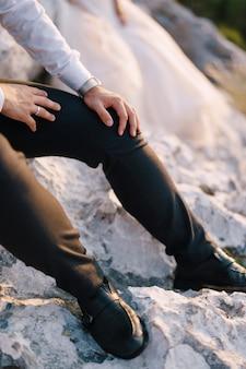 Foto de casamento no destino fineart em montenegro, mount lovchen, mãos do noivo com um relógio e um