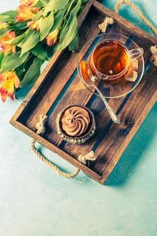 Foto de chá preto na xícara, bolo com creme