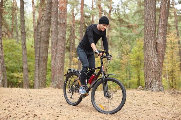 Foto de ciclista na trilha da floresta, viagem de bicicleta na natureza verde luxuriante, jovem cara atraente vestindo sportwear preto passeios em torno de árvores na floresta