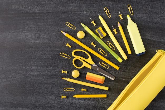 Foto de cima acima de vista aérea de conjunto de papel de carta amarelo e caixa de lápis colocados no lado direito, isolados no quadro-negro com espaço vazio em branco copyspace