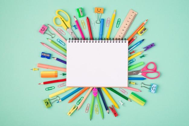 Foto de cima acima de vista aérea de papel de carta multicolorido e caderno em branco isolado em fundo turquesa com copyspace