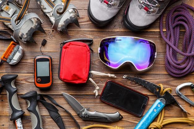 Foto de cima de bastões de esqui, botas, picareta, kits de primeiros socorros, máscaras em fundo de madeira.