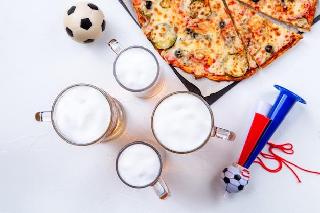 Foto de cima de copos com espuma de cerveja, pizza, cachimbos em fundo branco vazio