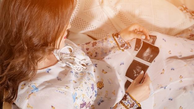 Foto de cima de uma mulher grávida segurando uma tomografia fetal sentada na cama