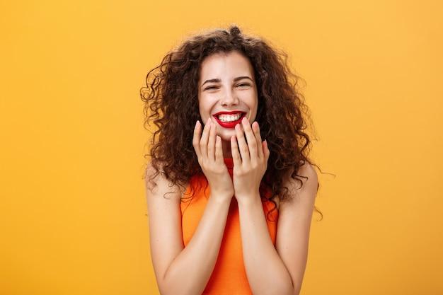 Foto de cintura de encantadora encantadora e fofa mulher caucasiana de cabelos encaracolados encantada em top recortado sendo tocada com palavras doces, sorrindo satisfeito segurando as palmas das mãos na linha da mandíbula surpreso e feliz sobre a parede laranja.