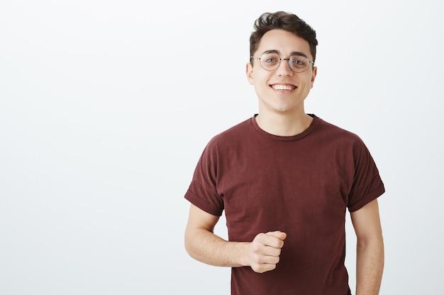 Foto de cintura de um estudante europeu despreocupado e feliz usando óculos redondos da moda e camiseta vermelha