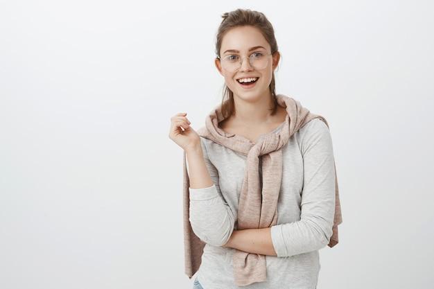 Foto de cintura de uma divertida sociável mulher europeia bonita com cabelo penteado, óculos e pulôver amarrado no pescoço gesticulando durante uma conversa e sorrindo amplamente e se sentindo interessada na conversa