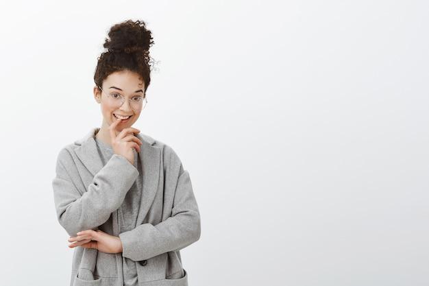Foto de cintura de uma mulher criativa inteligente de cabelos cacheados com penteado coque em óculos da moda e casaco cinza, mordendo o dedo e sorrindo com uma expressão intrigada