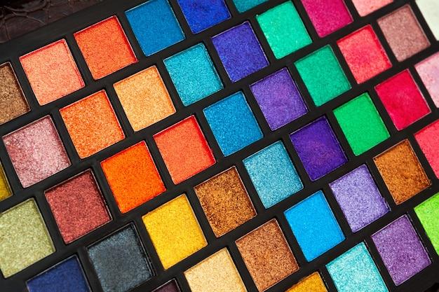 Foto de close da caixa com paleta de sombras multicoloridas, conjunto de maquiador