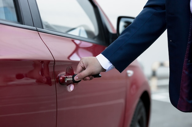 Foto de close da mão do empresário abrindo a porta do carro