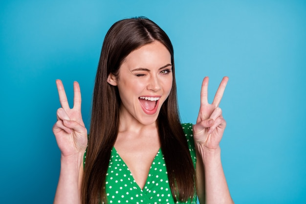 Foto de close de atraente senhora engraçada bom humor encantador aparência fofa mostrando símbolos de v-sinal mãos glamour piscando olho usar casual verde pontilhado singlet isolado fundo de cor azul