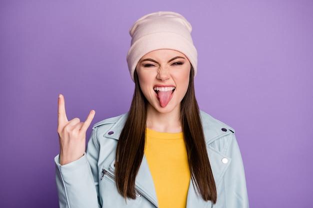 Foto de close de bom humor senhora bonita mostrando a língua para fora da boca provocando comportamento roqueiro louco mostrando chifres usar chapéu casual casaco moderno azul isolado fundo de cor roxa