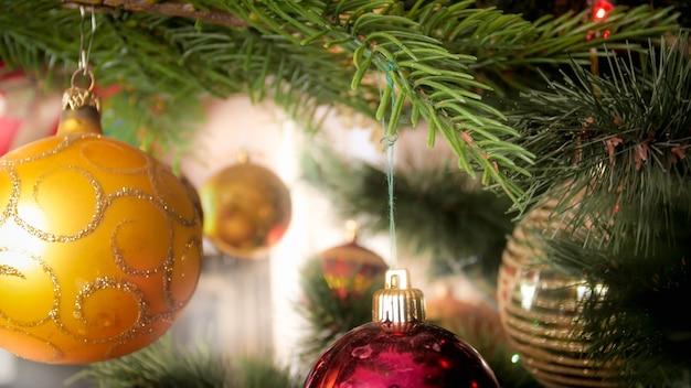 Foto de close de bugigangas douradas penduradas na árvore de natal decorada