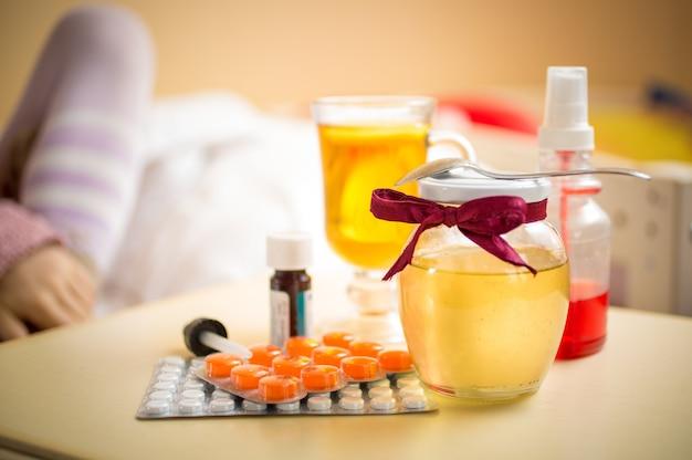 Foto de close de chá, pote de mel e comprimidos na mesa do quarto