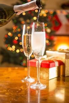 Foto de close de duas taças de champanhe na mesa sendo enchidas com a garrafa