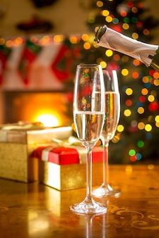 Foto de close de duas taças sendo cheias de champanhe na véspera de natal