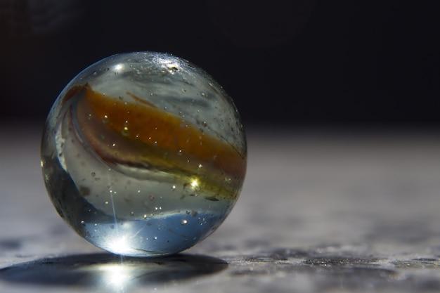 Foto de close de foco seletivo de uma esfera de vidro colorida coberta de gotas de água