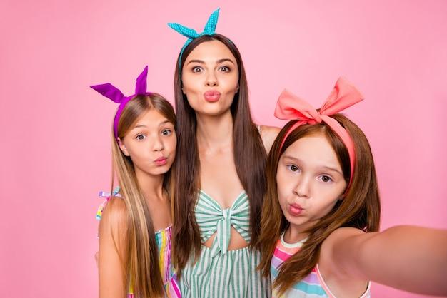 Foto de close de irmãs mais velhas com bandanas fazendo selfie mandando beijos no ar usando vestidos com saia isolada sobre fundo rosa