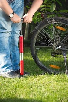 Foto de close de jovem bombeando roda de bicicleta na grama