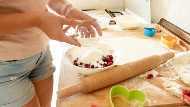 Foto de close de jovem cozinhando torta de frutas vermelhas com molho na cozinha de casa