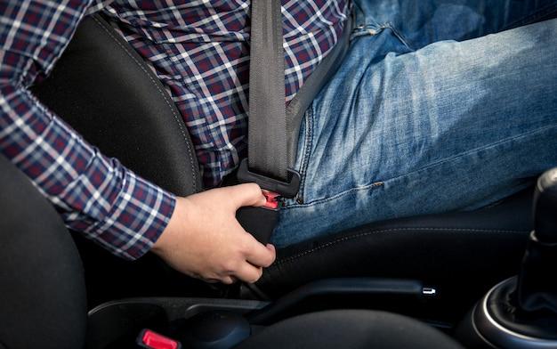 Foto de close de jovem sentado no banco do motorista e apertando o cinto