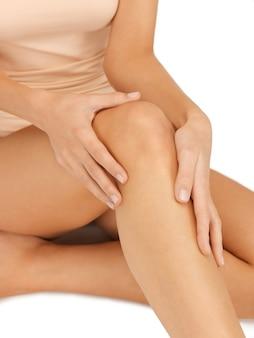 Foto de close de mãos femininas tocando o joelho