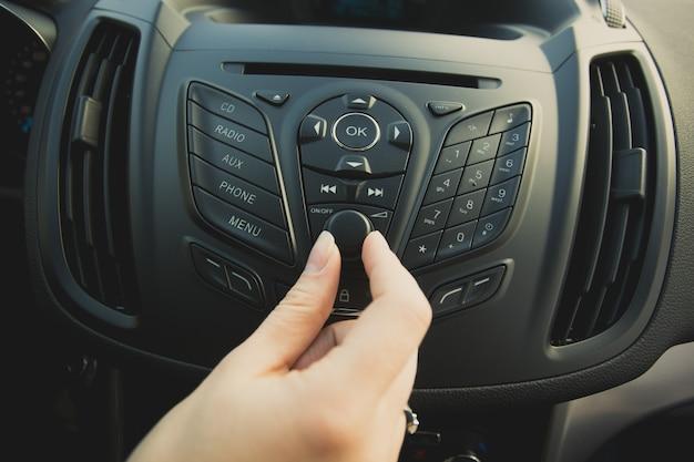 Foto de close de mulher ajustando o sistema de som do carro