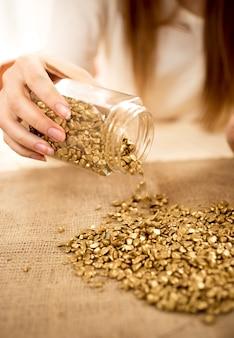Foto de close de mulher esvaziando barras de ouro com ouro na serapilheira
