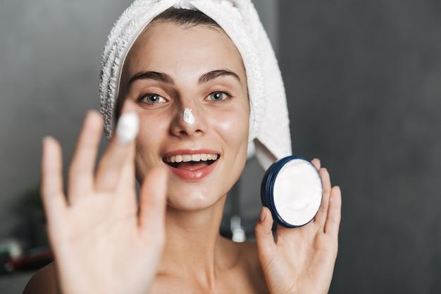 Foto de close de mulher feliz enrolada em uma toalha na cabeça, aplicando creme no rosto