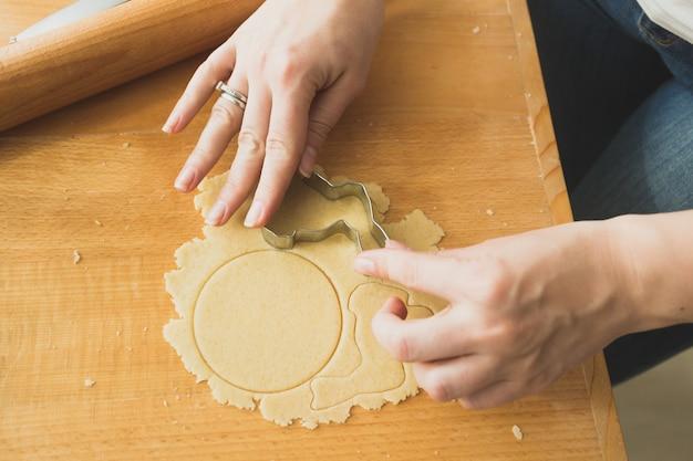 Foto de close de mulher usando cortador de biscoitos
