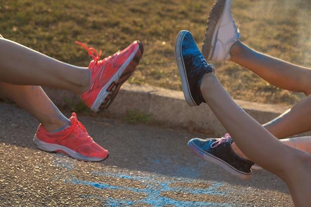 Foto de close de pés femininos coloridos cobertos com pó de holi azul