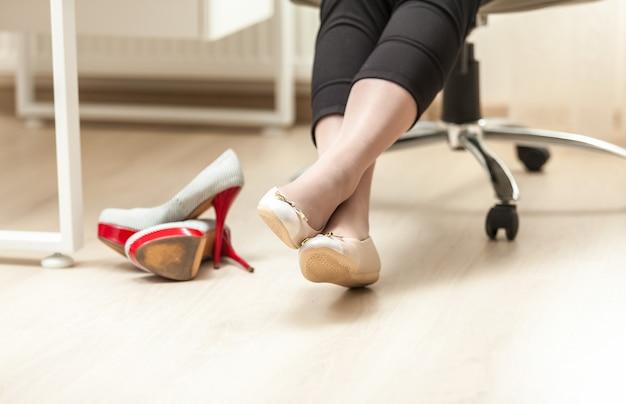 Foto de close de pés femininos no balé no escritório
