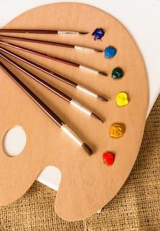 Foto de close de pincéis profissionais sobre paletes de madeira com tintas a óleo