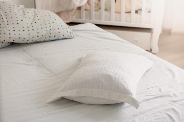 Foto de close de travesseiro branco na cama desarrumada em dia de sol