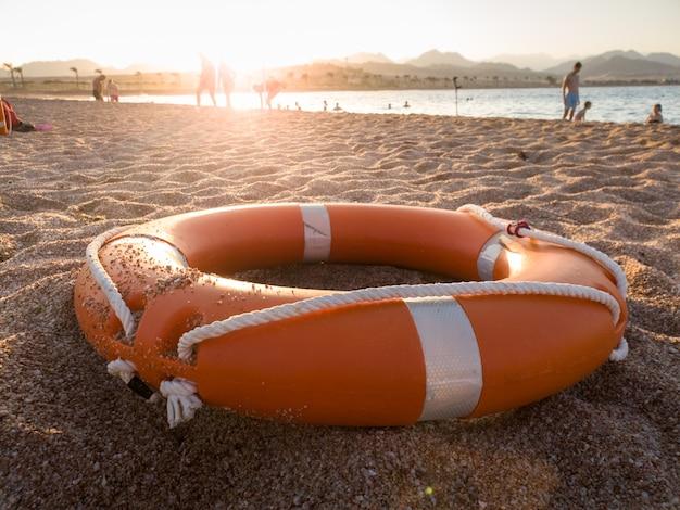 Foto de close de um anel de plástico laranja para salvar pessoas que estão se afogando no mar, deitado na praia