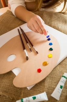 Foto de close de um artista profissional espremendo tinta a óleo de tubos em paletes de madeira